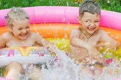 Dos niños que ríen y que flotan feliz en piscina inflable Fotografía de archivo