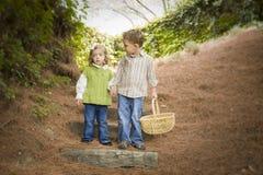 Dos niños que recorren abajo de los pasos de progresión de madera con la cesta Fotos de archivo
