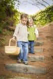 Dos niños que recorren abajo de los pasos de progresión de madera con la cesta Imágenes de archivo libres de regalías