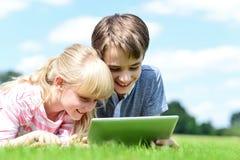 Dos niños que se acuestan y que usan la PC de la tableta Fotos de archivo