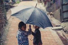 Dos niños que se ocultan debajo de un paraguas Imágenes de archivo libres de regalías