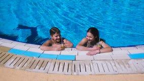 Dos niños que se relajan con el cóctel en piscina
