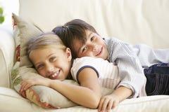 Dos niños que se relajan en Sofa At Home Foto de archivo