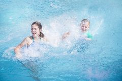 Dos niños que se salpican en la piscina mientras que el vacaciones foto de archivo