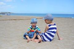 Dos niños que se sientan en la playa Fotografía de archivo