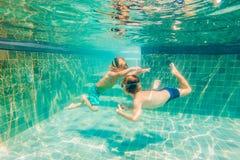 Dos niños que se zambullen en máscaras bajo el agua en piscina imagen de archivo libre de regalías