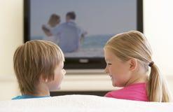 Dos niños que ven la TV con pantalla grande en casa fotografía de archivo