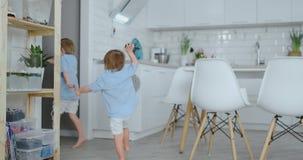 Dos niños saltan y gozan el correr en la casa en la cocina metrajes