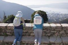 Dos niños se arrodillan en una pared de piedra en un pueblo de montaña en primavera temprana y miran abajo la bahía y la ciudad,  imagenes de archivo