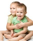 Dos niños se están divirtiendo mientras que se sientan en suelo Imágenes de archivo libres de regalías