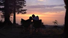 Dos niños se están sentando en el mar y la charla almacen de metraje de vídeo