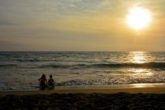 Dos niños se sientan en el ocaso en la playa Imágenes de archivo libres de regalías