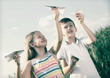 Dos niños sonrientes que juegan con los aviones de papel simples Imágenes de archivo libres de regalías