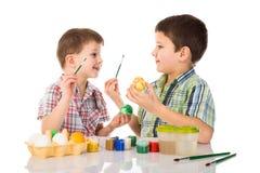 Dos niños sonrientes que pintan los huevos de Pascua Imagen de archivo