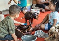 Dos ni?os trabajan en el negocio de Sari Pertiwi Wood Carving, Juga, Bali, Indonesia foto de archivo