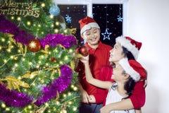 Dos niños y su madre con el árbol de navidad Imagen de archivo libre de regalías