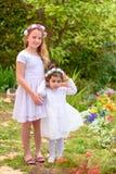Dos ni?as en los vestidos blancos y la guirnalda de la flor que se divierte un jard?n del verano imagenes de archivo