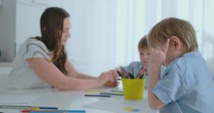 Dos ni?os de muchachos dibujan con su madre que se sienta en la cocina almacen de video