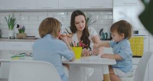 Dos ni?os de muchachos dibujan con su madre que se sienta en la cocina Familia feliz en el pa?s metrajes