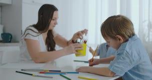 Dos ni?os de muchachos dibujan con su madre que se sienta en la cocina Familia feliz en el pa?s Los hermanos dibujan en la tabla  metrajes