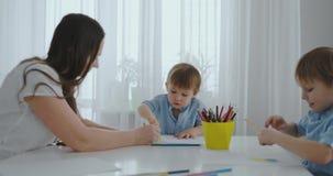 Dos ni?os de muchachos dibujan con su madre que se sienta en la cocina Familia feliz en el pa?s Los hermanos dibujan en la tabla  almacen de video
