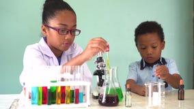 Dos ni?os mezclados afroamericanos que prueban el experimento del laboratorio de qu?mica almacen de metraje de vídeo