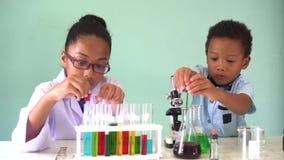 Dos ni?os mezclados afroamericanos que prueban el experimento del laboratorio de qu?mica almacen de video