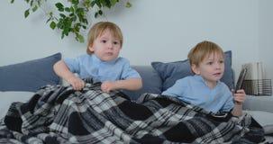Dos ni?os miran a un programa de televisi?n emocionante en la TV Dos hermanos est?n viendo la TV metrajes