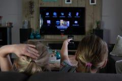Dos ni?os que resbalan a trav?s de los apps en una TV elegante detrás de los niños con el foco en el teledirigido foto de archivo
