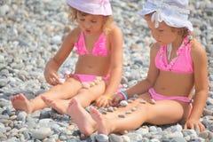 Dos niñas están jugando con las piedras del guijarro Foto de archivo libre de regalías