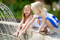 Dos niñas lindas que juegan con una fuente de la ciudad en día de verano caliente Foto de archivo