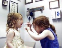Dos niñas que juegan al doctor Imágenes de archivo libres de regalías