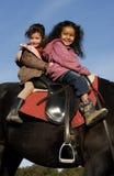 Dos niñas que montan Imagen de archivo
