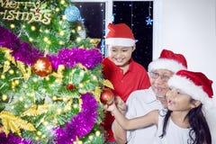 Dos nietos adornan un árbol de navidad en casa Fotografía de archivo