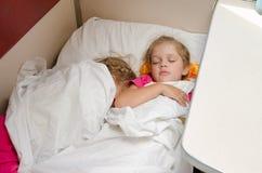 Dos niños duermen en el tren en la misma ubicación de tierra en el carro de segunda clase del compartimiento Foto de archivo
