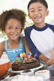 Dos niños en cocina con la torta de cumpleaños Foto de archivo
