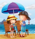 Dos niños en la playa cerca de las sillas de madera Fotos de archivo