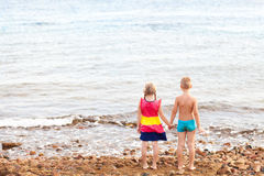 Dos niños en la playa que mira el mar Fotos de archivo