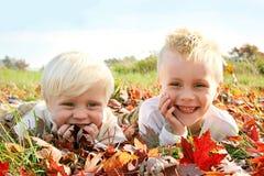 Dos niños jovenes felices que juegan afuera en hojas de la caída Imágenes de archivo libres de regalías