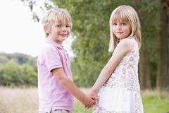 Dos niños jovenes que se colocan al aire libre que llevan a cabo las manos Fotografía de archivo