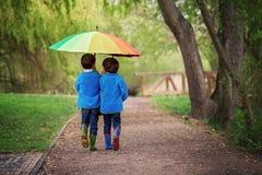 Dos niños pequeños adorables, caminando en un parque en un día lluvioso, juegan Fotos de archivo libres de regalías