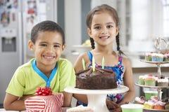 Dos niños que hacen una pausa la tabla puesta con la comida de la fiesta de cumpleaños Imágenes de archivo libres de regalías