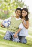 Dos niños que juegan al balompié en parque Imagenes de archivo