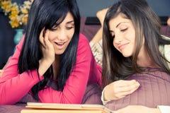 Dos noticias sonrientes de la lectura de las muchachas en la tableta en red social fotografía de archivo
