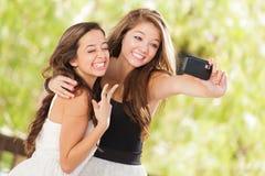 Dos novias adolescentes de la raza mixta atractiva que toman Selfies Fotografía de archivo