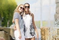 Dos novias adolescentes junto Presentación contra la fuente en parque al aire libre Fotografía de archivo libre de regalías