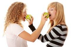 Dos novias adolescentes que comen manzanas verdes Imagenes de archivo