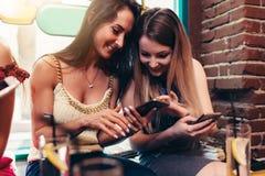 Dos novias alegres que usan el teléfono que mira la pantalla que sonríe mientras que desayunando en el café Foto de archivo libre de regalías