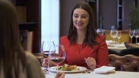 Dos novias bonitas que se sientan en el restaurante moderno delante de uno a Muchacha que le cuenta historia interesante almacen de video