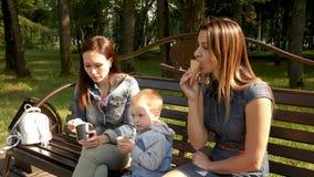 Dos novias con un niño se sientan en un banco en el parque de la ciudad y comen el helado Pares homosexuales, mujeres lesbianas j almacen de metraje de vídeo